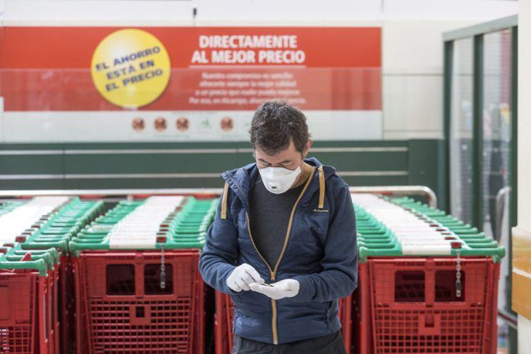Un hombre mira su móvil en un supermercado de Madrid.