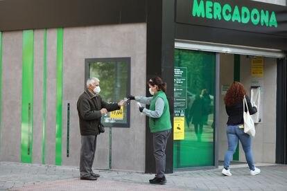 Una trabajadora de un supermercado madrileño reparte guantes a los clientes.