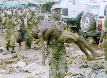 Un <i>casco azul</i> de la ONU lleva en brazos a un refugiado asesinado por el Ejército ruandés.