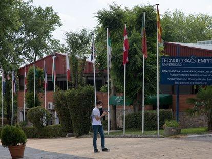 Un joven pasa delante de un cartel en español, inglés, alemán y chino que da la bienvenida a la Universidad Tecnología y Empresa en el campus del Colegio Nuevo Centro, en el distrito de Villaverde de Madrid.