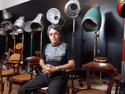 Raffel Pages sentado junto a algunos de los secadores de casco eléctricos de su colección.