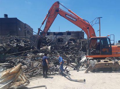 Trabajadores de la fábrica de colchones Foamco, destruida en un ataque israelí, retiran escombros, el domingo en Gaza.