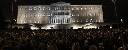 Participantes en una marcha silenciosa en solidaridad con el gobierno griego frente al Parlamento de Atenas.
