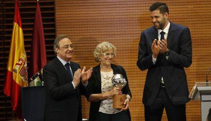 Manuela Carmena, este jueves en el Ayuntamiento de Madrid junto a Florentino Pérez y Felipe Reyes.