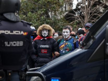 Un agente antidistrubios, frente a manifestantes con máscaras de Anonymous convocados por la asociación de policías y guardias civiles Jusapol
