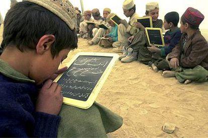 Un grupo de niños refugiados afganos en Pakistán practica caligrafía arábiga en sus pizarras.