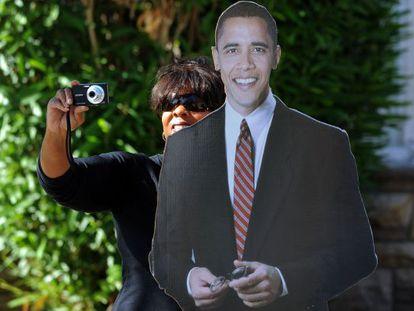 Una partidaria de Obama toma fotos, tras una figura de cartón del presidente.