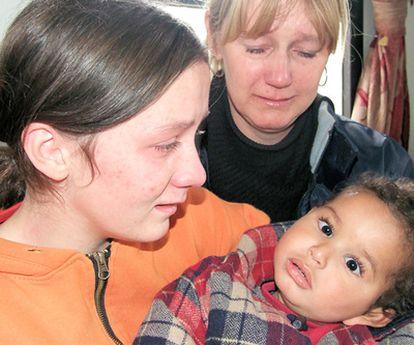 Dos cuidadoras se despiden de un niño recogido en el orfanato Village of hope.