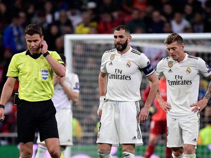 El árbitro Felix Brych en el partido de este martes. Detrás, los jugadores del Madrid Benzema (izquierda) y Kroos.