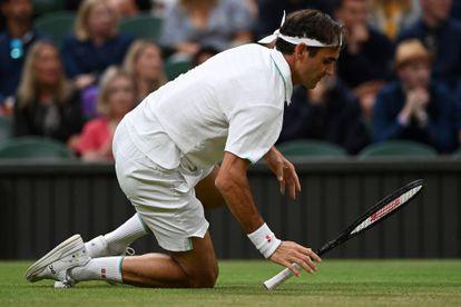 Federer cae sobre la hierba durante el partido contra Sonego.