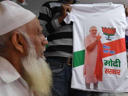 Un comerciante muestra una camiseta con la figura del primer ministro indio Narendra Modi en una tienda de Nueva Delhi el pasado 13 de marzo.