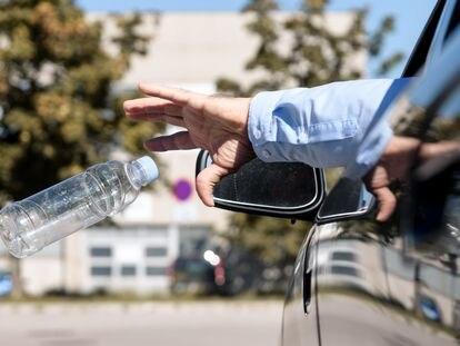 Un hombre arroja una botella de plástico vacía por la ventanilla de su coche.