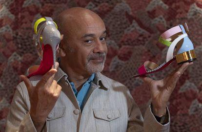 El diseñador Christian Louboutin, con dos de los zapatos que se venden en su nueva tienda de Barcelona.