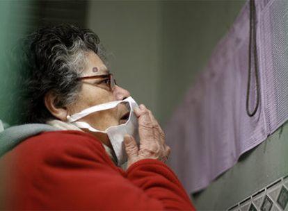 Una mujer con la mascarilla para evitar el contagio de la nueva gripe consulta el padrón electoral en una escuela de Argentina