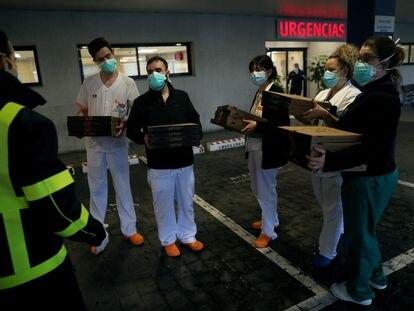 Personal sanitario del Hospital Madrid Sanchinarro recoge unas pizzas a la entrada de Urgencias.
