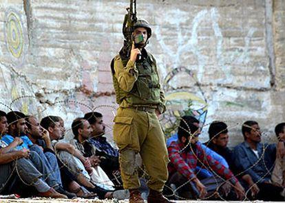 Un soldado irsraelí custodia a detenidos palestinos en un campo de refugiados de Nablús.