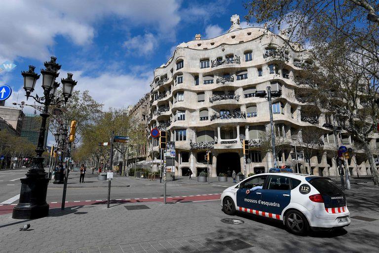 Un coche de los Mossos delante de la Pedrera de Gaudí, en Barcelona, vacía durante el confinamiento.