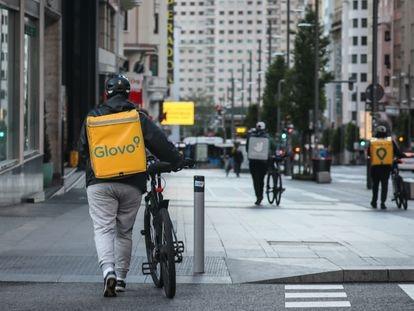 Dos repartidores de Glovo y otro de Deliveroo caminan por Gran Vía de Madrid, en abril de 2020.