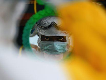 Un trabajador sanitario comprueba su equipo de protección en Kailahun (Sierra Leona) en agosto de 2014 durante el brote de ébola de África occidental.