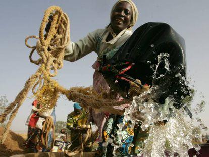 Una agricultora toma agua de un pozo para regar los cultivos, en Níger.