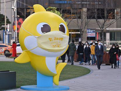 Transeúntes caminan junto a una estatua de uno de los personajes del vídeo de 'Baby Shark' en una plaza de Seúl (Corea del Sur).