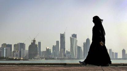 Una mujer camina frente a los rascacielos de Doha, Qatar.