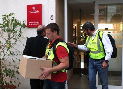 Agentes con documentación saliendo de Servicios Sociales.