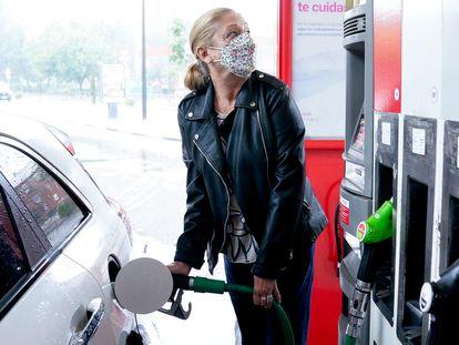 Una mujer reposta gasolina a su vehículo en Madrid, en junio.