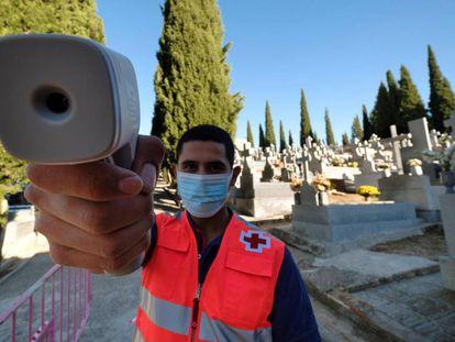 Un vigilante toma la temperatura en el cementerio de Toledo.