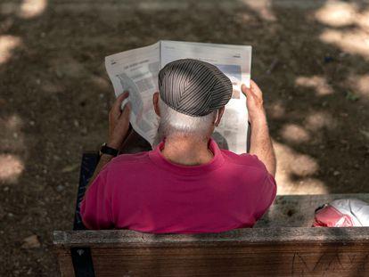 Un hombre lee el periódico en un parque.