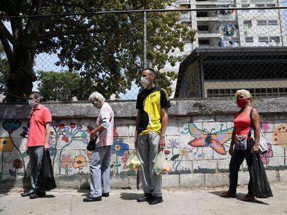 Habitantes de Caracas hace fila para acceder a un mercado de verduras, este jueves.