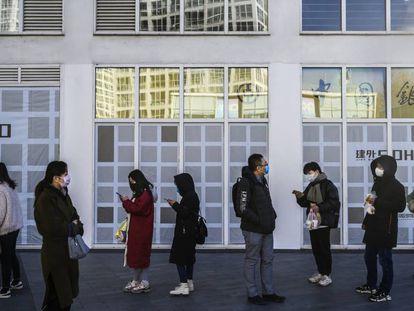 Varios trabajadores, a las puertas de su oficina en Pekín.