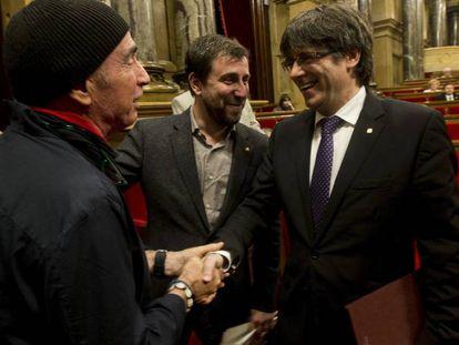 Llach (i) y Puigdemont se dan la mano en presencia de Comín.