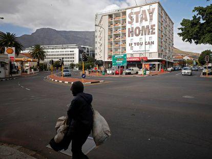 Un hombre pasa por delante de un cartel que pide a los ciudadanos que se queden en casa en Ciudad del Cabo, Sudáfrica, este jueves 26 de marzo. Hoy empieza el periodo de cuarentena de 21 días en este país para intentar contener el coronavirus.
