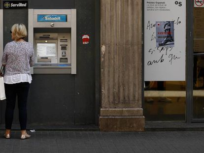 Clientes sacan dinero de un cajero.