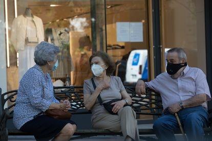 Unos jubilados conversan en un banco, en Madrid.