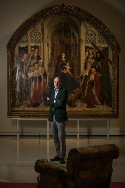 Joan Oliveras entre el sillón creado por Tàpies y la obra gótica de Dalmau que puede verse dentro de la exposición 'Intrusos' del MNAC, el museo que él preside.