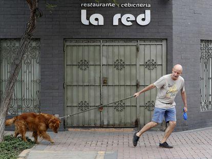 Un hombre pasea a su perro durante el confinamiento, en Lima (Perú).
