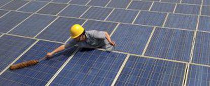 Un trabajador limpia paneles solares.