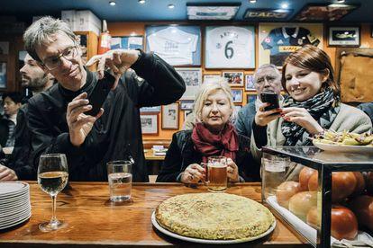 Unos comensales fotografían la famosa tortilla del bar Nestor, en San Sebastián.