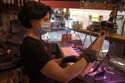 Una empleada corta jamón en la charcutería Casa Bartolomé, fundada en Madrid en 1837.