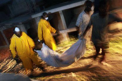 Trabajadores haitianos trasladan el cadáver de un muerto por el cólera en un cementerio en Puerto Príncipe.