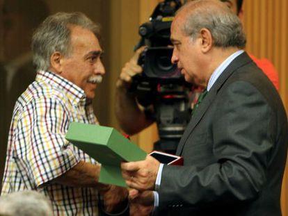 José Manuel Alfonso García, víctima del atentado de ETA a Hipercor hace 25 años, recibe en Barcelona la encomienda de manos del ministro de Interior, Jorge Fernández Díaz.