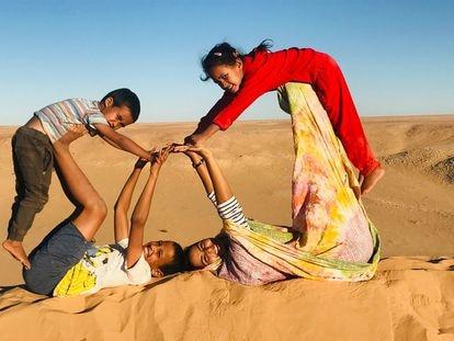Nana (a la derecha, vestida de color amarillo) juega con otros niños en el Sáhara.