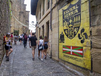 Un grupo de jóvenes pasa delante de un mural a favor de la independencia en una calle de Pasajes de San Juan (Gipuzkoa).