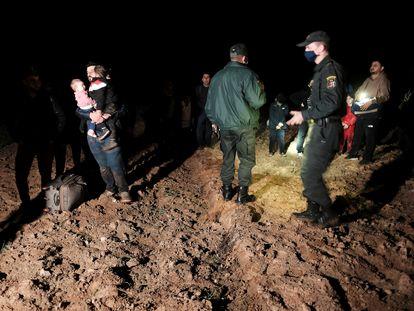 Un agente fronterizos lituano junto a migrantes detenidos cerca de la localidad de Vorzova tras llegar desde la vecina Bielorrusia este miércoles