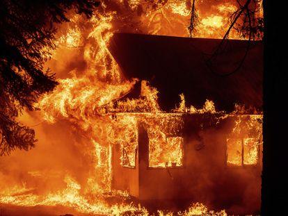 El incendio que empezó en Dixie amenaza con destruir hasta 10.000 edificios, como el que se aprecia en esta imagen de este domingo