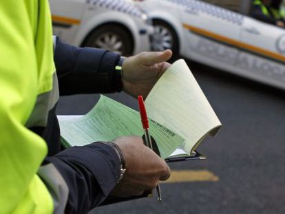 Un agente de la Policía Local de Sevilla rellena el papeleo de una multa.
