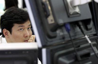 Un operador sigue las cotizaciones en su monitor en la Bosla de Seúl.