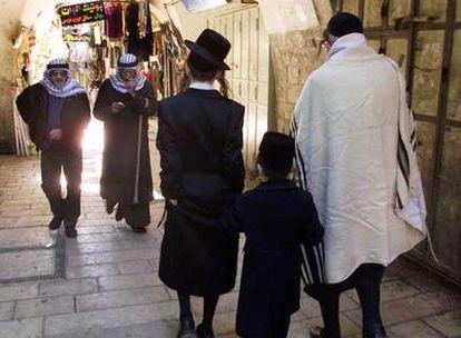 En un mercado de Jerusalén,  tres judíos (en primer plano) y dos musulmanes, en 2001.R